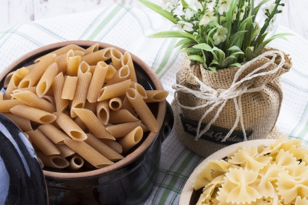 Raw food composition - yelow colored farfelle and brown penne pasta in a clay pot on a bright wooden background. photo