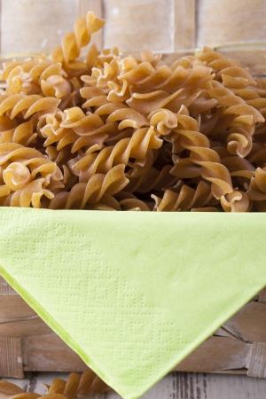 rotini: Composici�n de los alimentos crudos - marr�n pasta rotini coloca sobre un fondo brillante.