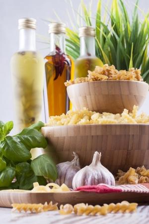 rotini: Composici�n de los alimentos crudos - rotini amarillo y marr�n en un taz�n de madera colocado sobre un fondo brillante.