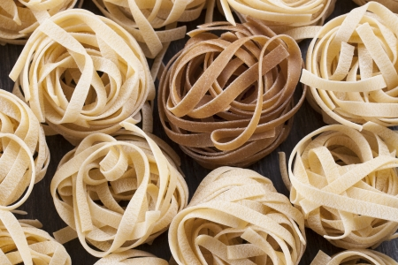 Raw food composition - yellow and brown tagliatelle pasta on a dark background. Stock Photo