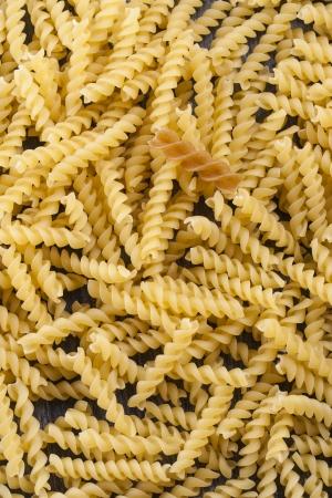 rotini: Composici�n de alimentos crudos - amarillo y marr�n Rotini pasta como fondo abstracto.
