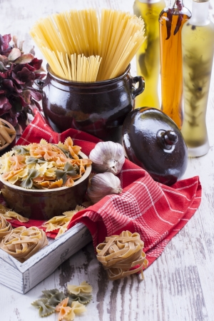 Raw food composition - brown penne, yellow, orange and green farfalle, brown tagliatelle and yellow spaghetti  pasta in a clay pot placed on a bright wooden background.