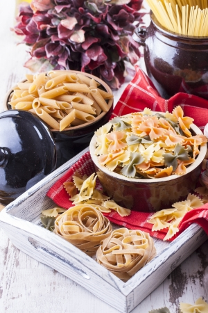 Raw food composition - brown penne, yellow, orange and green farfalle, brown tagliatelle and yellow spaghetti  pasta in a clay pot placed on a bright wooden background. photo
