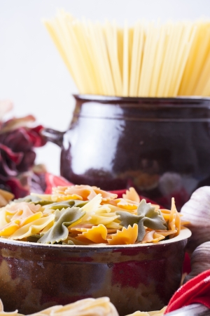 Raw food composition - yellow, orange and green farfalle and yellow spaghetti  pasta in a clay pot placed on a bright wooden background. photo