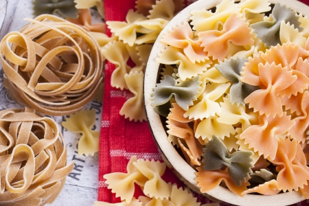 Raw food composition - yellow, orange and green farfalle, brown tagliatelle in a clay pot placed on a bright wooden background. photo