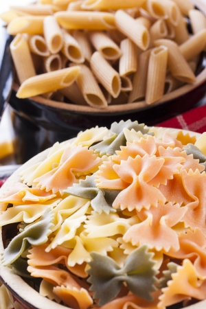 Raw food composition - yellow, orange and green farfalle, brown tagliatelle pasta in a clay pot placed on a bright wooden background. photo