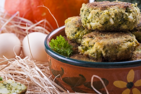 Homemade frayed Broccoli chops in the clay pot placed on a wooden shavings. Stock Photo