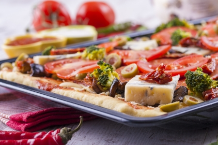 Close up photo of homemade pizza ready to baking placed on a black tray. Stock Photo