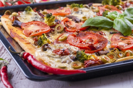 Close up of the just baked homemade pizza with tomato, salami slices and olives placed on a black tray. Stock Photo