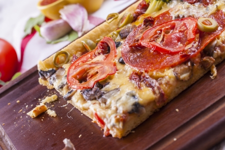 Close up of the just baked homemade pizza with tomato, salami slices and olives placed on brown cutting board.