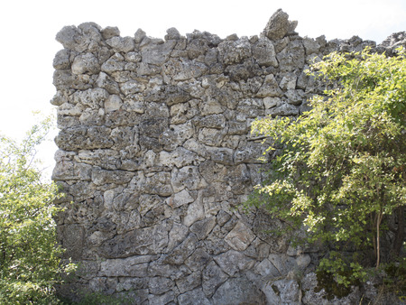 overbuilding: White stone wall built of stones against the sky