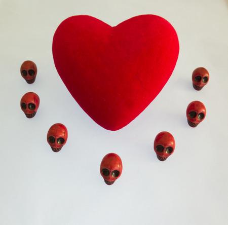 red velvet: Red velvet heart surrounded by red skulls on a white background