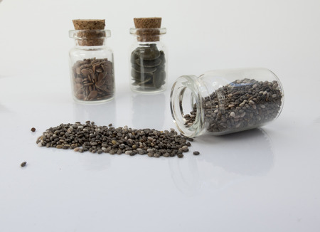 dietetics: Glass bottle with cork with flax seed and pumpkin and chia. study of super food