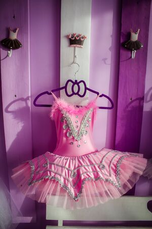 A ballet dress, a pink tutu, hangs on a decorative board with hooks on a hanger.