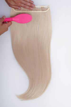 Straight blond remy virgin human hair clip in extensions on light grey background