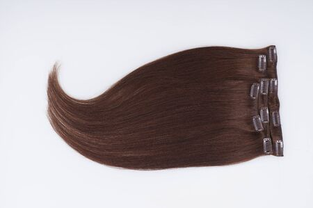 Straight virgin remy brown human hair clip in extensions on light grey background