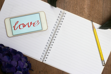 single word: Word of love in smart phone and blank book with flower on old desk