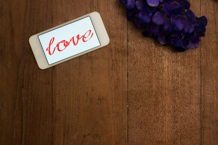 single word: Word of love in smart phone and flower on old desk