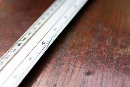 Close up of old steel ruler on the brown wooden background with scratches, Tools for measuring length on table,Work and education concept