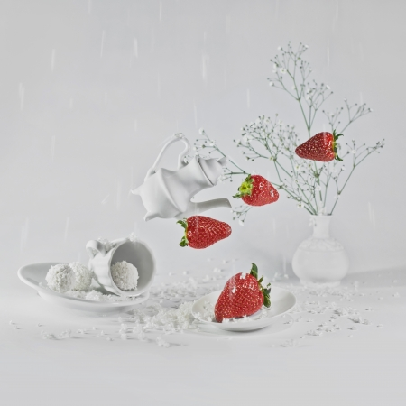 levitating: Levitating strawberry and small decorative dishes in white background