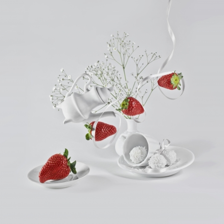 levitating: Levitating strawberry with white ribbon, litle flowers and small decorative dishes  Stock Photo