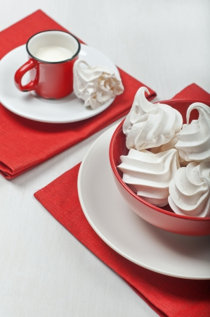 lucid: View of a red bowl with white meringues on a red textile napkin  In the distance is a red cup with milk and a broken piece of meringue on a plate  Stock Photo