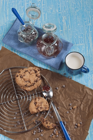 Top view of cookies with chocolate drops on round iron stand and brown paper,cup of milk,  jars with jam and chocolate on cracked blue background photo