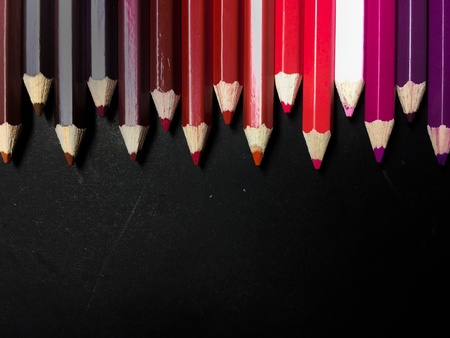 artistic: Warm tone colour pencils row on black background.