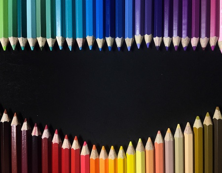 Photo frame of multicolour pencil on black background