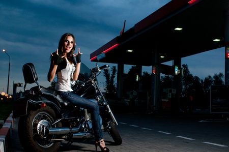 Model on the motorcycle on gas station, night shot photo