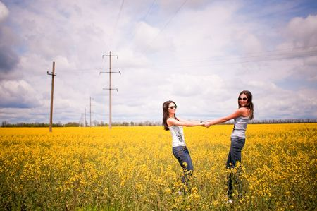 sunglassess: attractive young girls are playing in the field of flowers Stock Photo