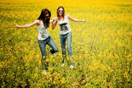 attractive young girls are playing in the field of flowers photo