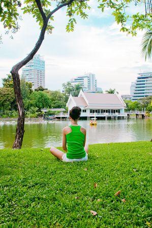 girl meditating in the park near the river, in bangkok photo