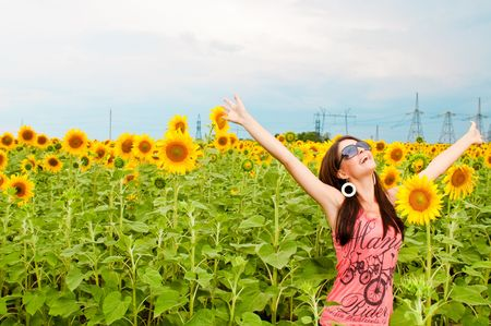 woman having fun in the field full of sunflowers photo