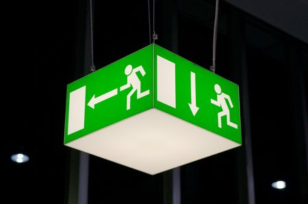 Green emergency exit sign, cube-shaped, hanging from a ceiling. photo