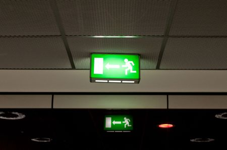 Green emergency exit sign,  hanging from a ceiling. photo