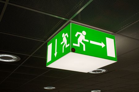 warning back: Green emergency exit sign, cube-shaped, hanging from a ceiling.