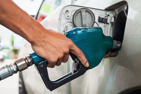tanque de combustible: mantenga la boquilla de combustible para añadir combustible en el coche en la gasolinera Foto de archivo