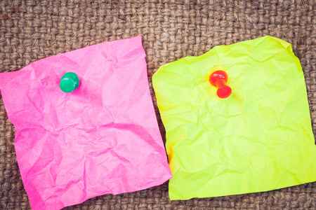 thumbtack: Note paper pink and green with push pins on cloth sack background Stock Photo