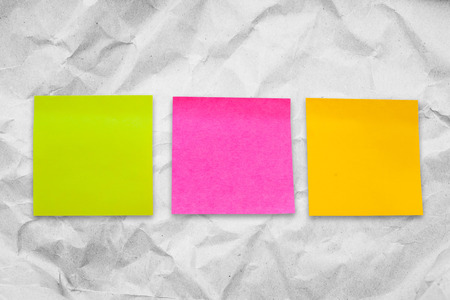post it,pink,yellow,on crumpled paper background Stock Photo