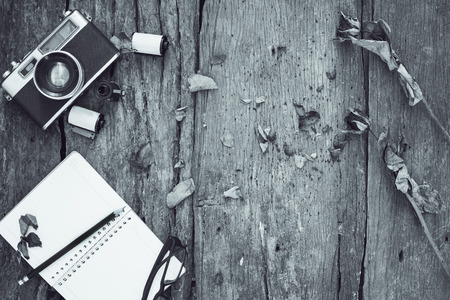 blackwhite image notebook,pencil,camera,film and dried roses on vintage background