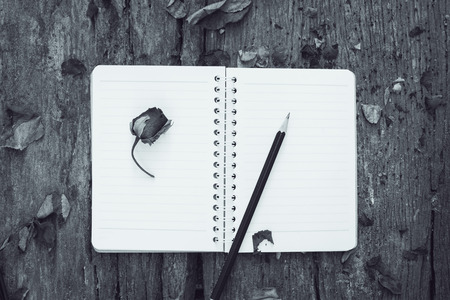 blackwhite image notebook,pencil and dried roses on vintage background