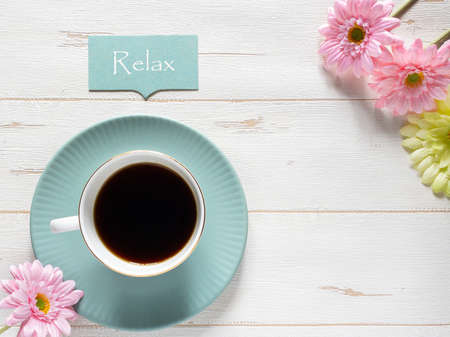 "Coffee and ""Relax"" message on blue plate, white wood background"