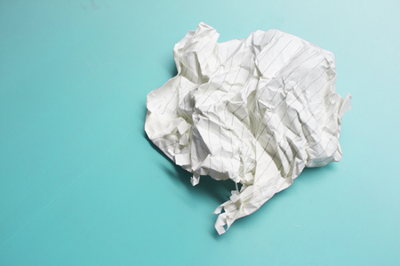 Crumpled paper sheet on green background