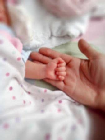 entregar el bebé durmiendo en la mano del primer plano de la madre. imagen borrosa.