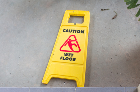 alerts: Yellow sign that alerts for wet floor. Stock Photo