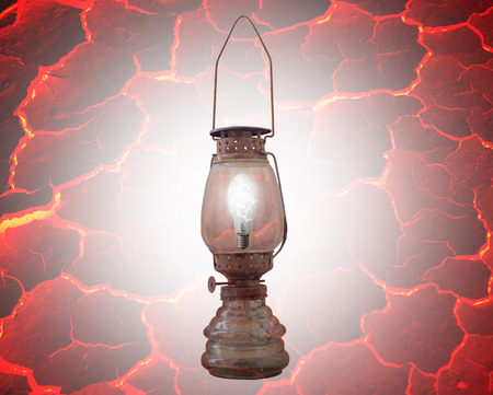 red oil lamp: Old dusty rusty oil lamp with a light bulb inside. isolated on red Stock Photo
