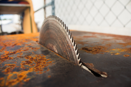 Circular saws and sawdust in workshop. Close up of table saw blade, outdoors.
