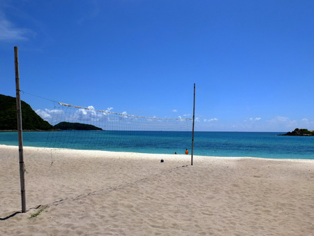 a beach volleyball net beside the sea photo