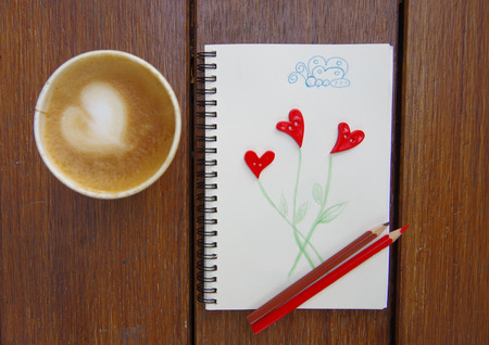 cup of coffee with cookie and drawing, studs shaped heart photo